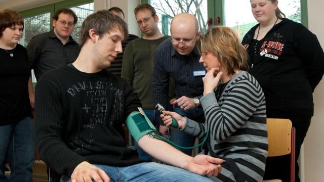 Altenpflegeschüler lernen im Fachseminar für Altenpflege, den Blutdruck zu messen. (Foto: SMMP/Pohl)