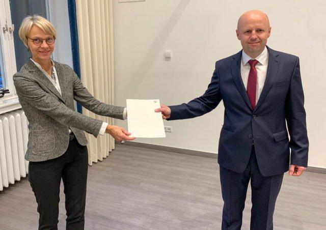 Regierungspräsidentin Dorothee Feller überreicht Edis Ahmetspahic den Bewilligungsbescheid